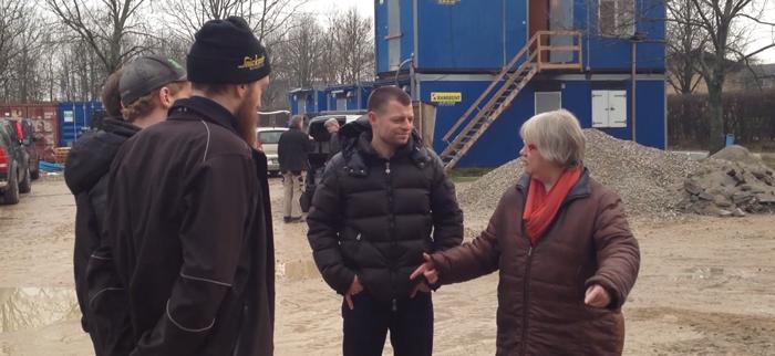 Billede af Lene Davidsen, der snakker med mænd på en byggeplads.
