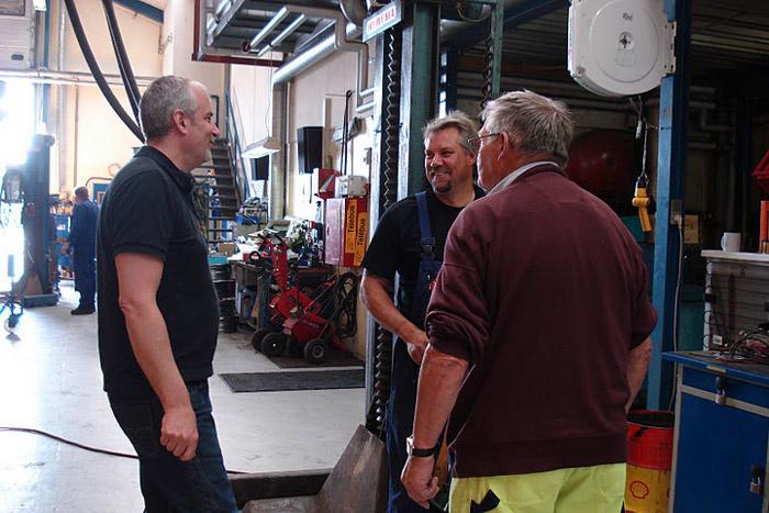 Billede af tre mænd, der er på arbejde. De snakker og griner sammen.