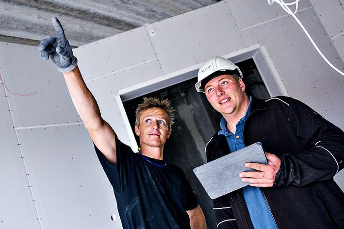 Billede af to mænd, der er på arbejde. Manden til venstre peger op imod venstre hjørne af billedet, og de kigger begge to i samme retning.