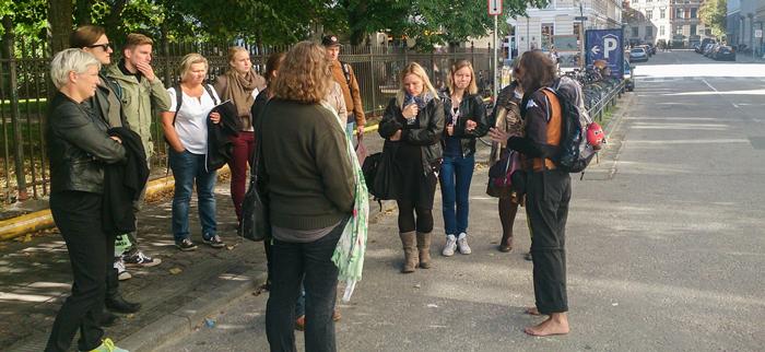 Billede af en gruppe mennesker, der hører på en hjemløs, der fortæller.