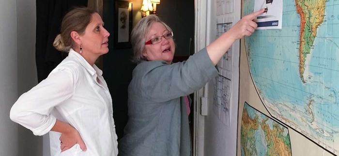 Billede af Lene Davidsen og en kvinde, der begge ser på et papir på en væg.
